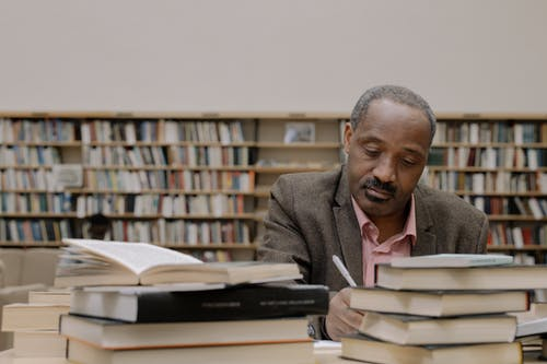 Man in Gray Suit Jacket Sitting Beside Books