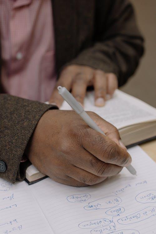 Persona En Camisa De Vestir De Cuadros Vichy Rosa Y Blanco Con Lápiz Escribiendo Sobre Papel Blanco