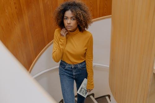 Wanita Dengan Kemeja Lengan Panjang Kuning Dan Jeans Denim Biru