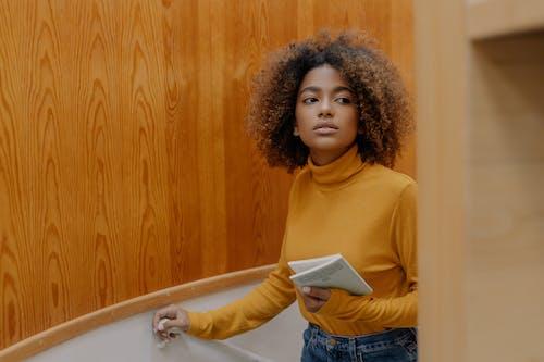 Gadis Di Buku Memegang Sweater Kuning