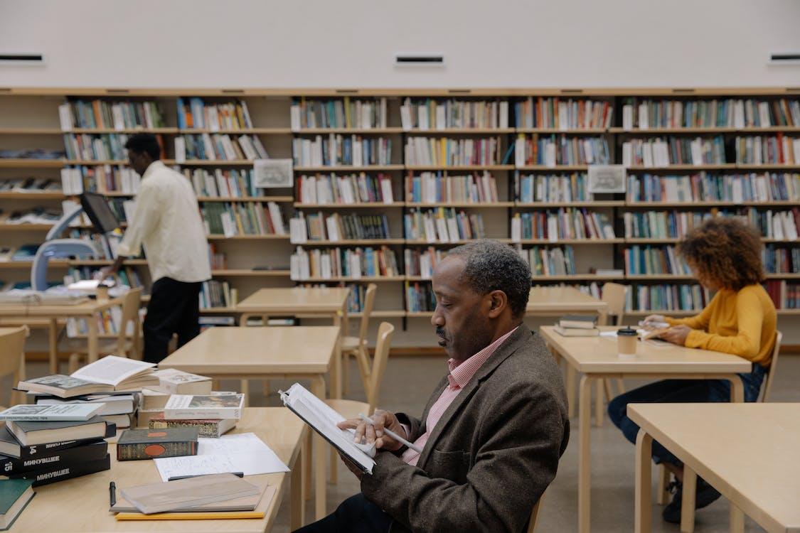 Man in Brown Coat Reading Book
