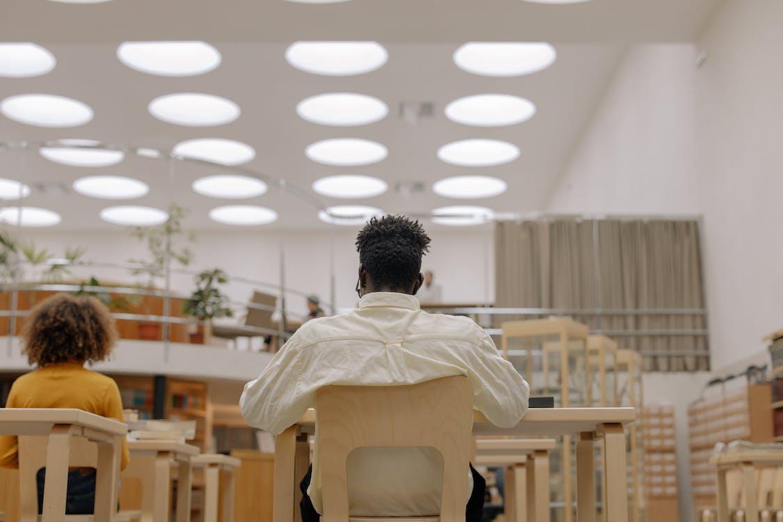 Homme En Chemise Blanche Assise Sur Une Chaise Noire