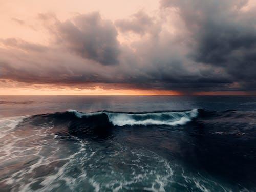 Olas Del Océano Bajo El Cielo Nublado Durante La Puesta De Sol