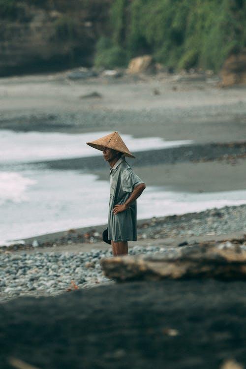 Woman in Blue Dress Wearing Brown Hat Standing on Seashore