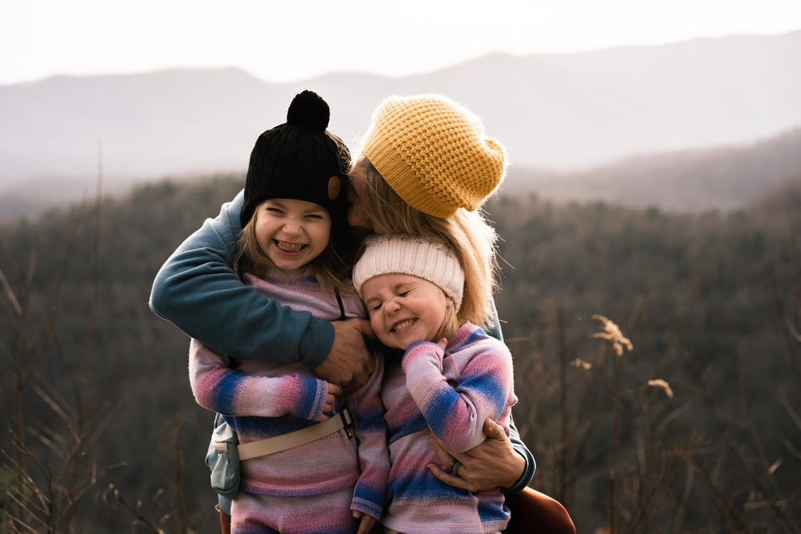 Woman in Gray Long Sleeve Shirt Carrying Girl in Blue Jacket