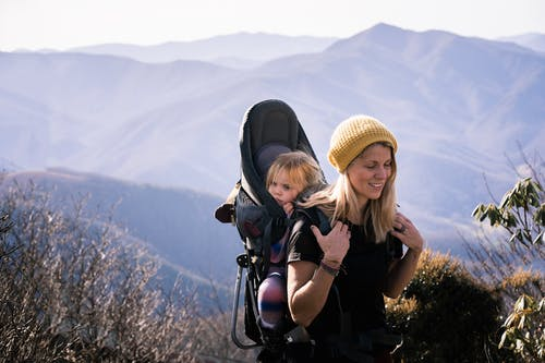 Woman in Black Shirt Carrying Girl in Black Jacket on Mountain