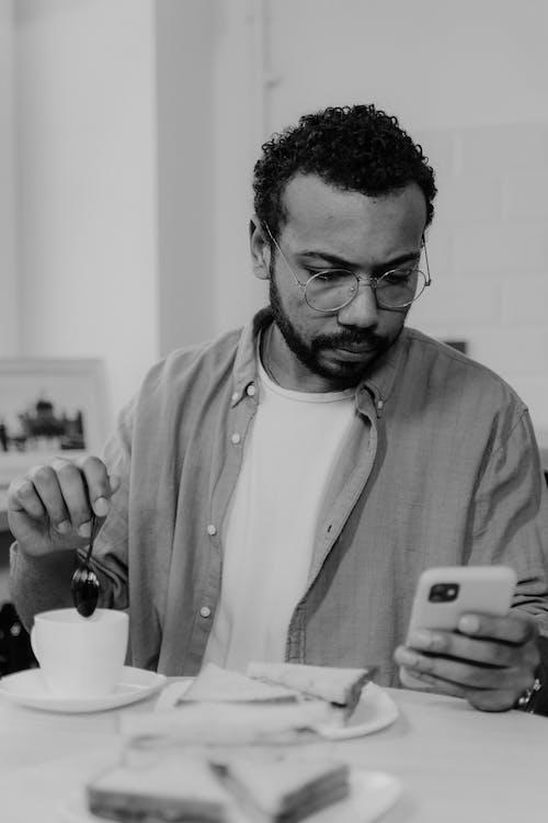 Man Using a Phone While Having Coffee