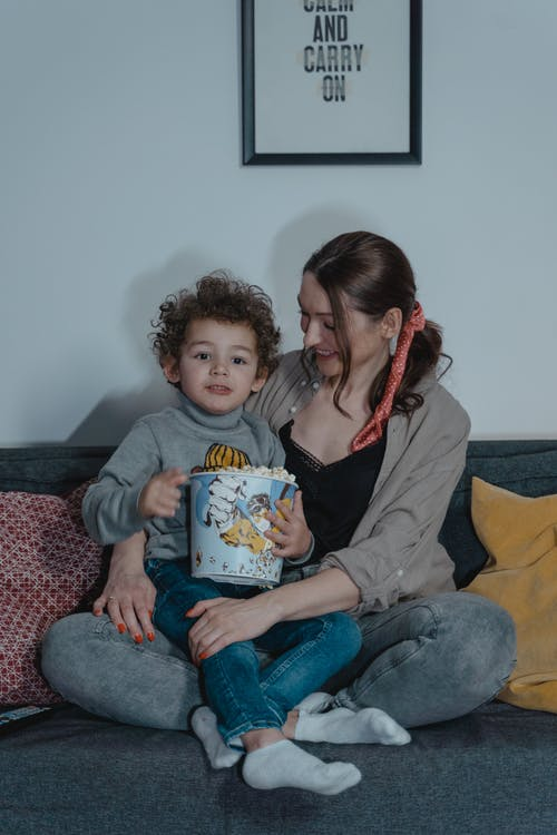 Woman and a Child Sitting on a Sofa Eating Popcorn