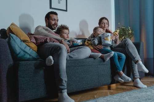 Family Sitting on a Sofa Eating Popcorn