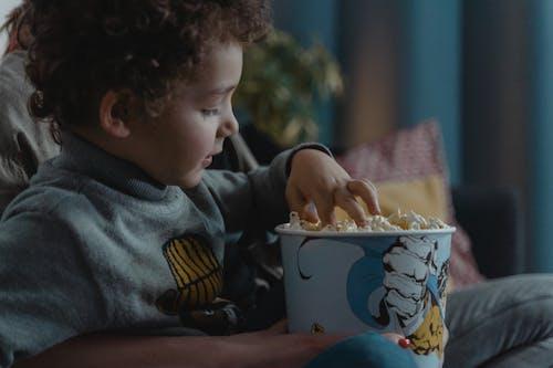 Boy Wearing Gray Sweater Eating Popcorn