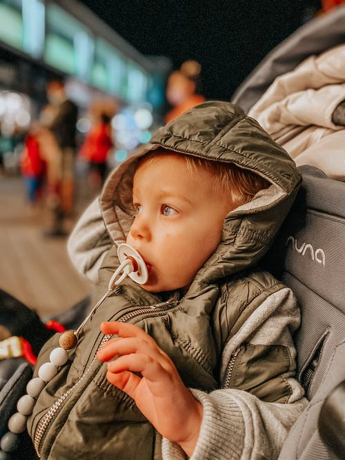 Child Wearing a Hoodie Jacket Sitting on a Stroller