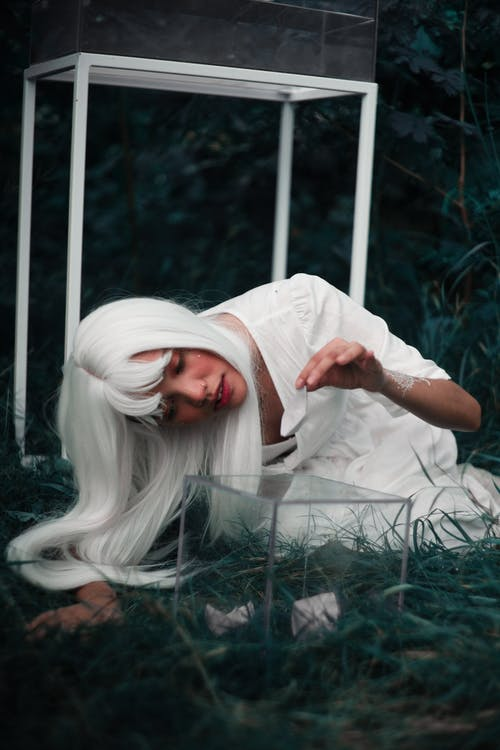 Mysterious Asian female in white wig and white dress sitting on meadow placing origami boats in glass box in summer day