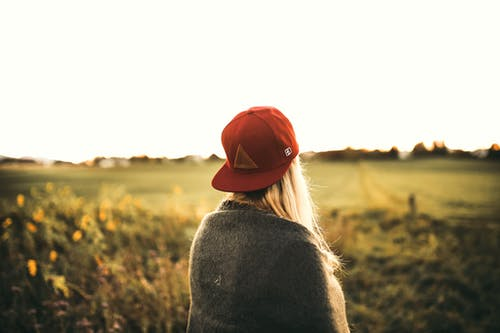 Woman in Gray Cardigan and Red Snapback Cap