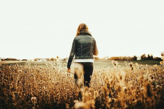 Woman in Blue Denim Jacket Walking on Field
