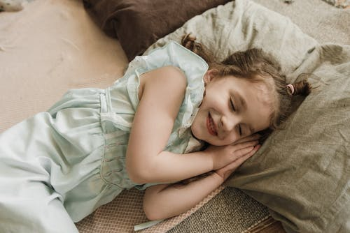 Girl in Green Dress Lying on Brown Textile