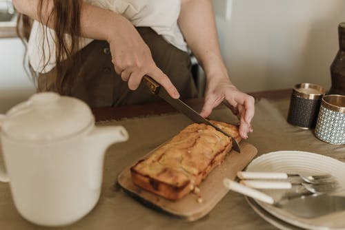 Crop anonymous female with long dark hair in casual clothes cutting appetizing sweet banana bread while standing at table in kitchen