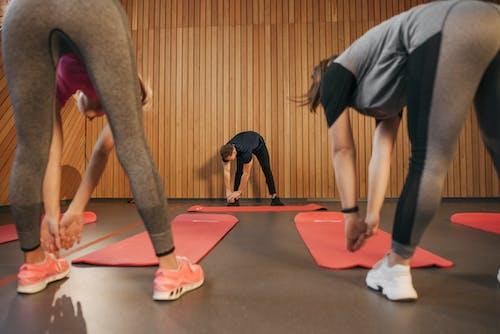 People In the Gym Bending Forward