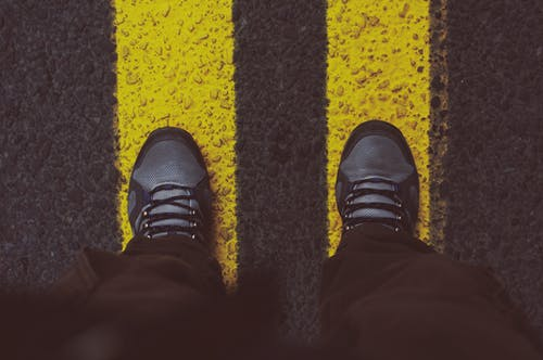 Person in Gray Sneakers Standing on Pedestrian Lane