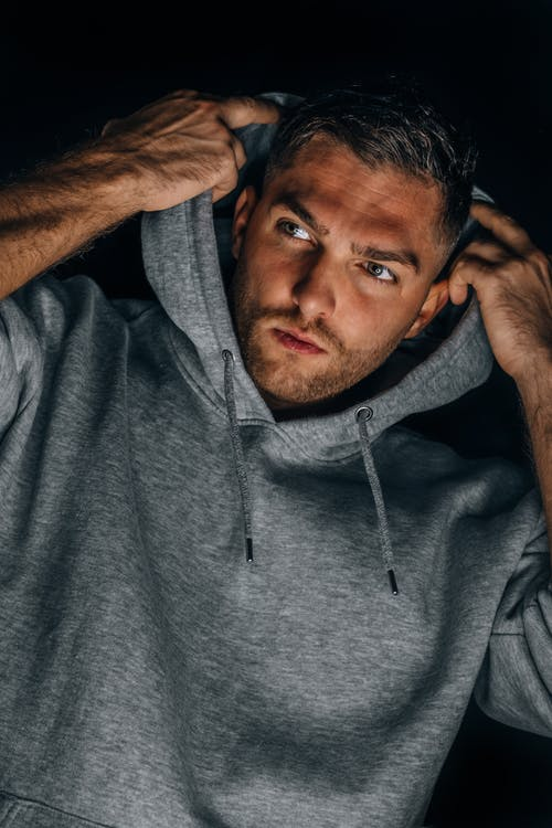 Man in Gray Hoodie Covering His Face