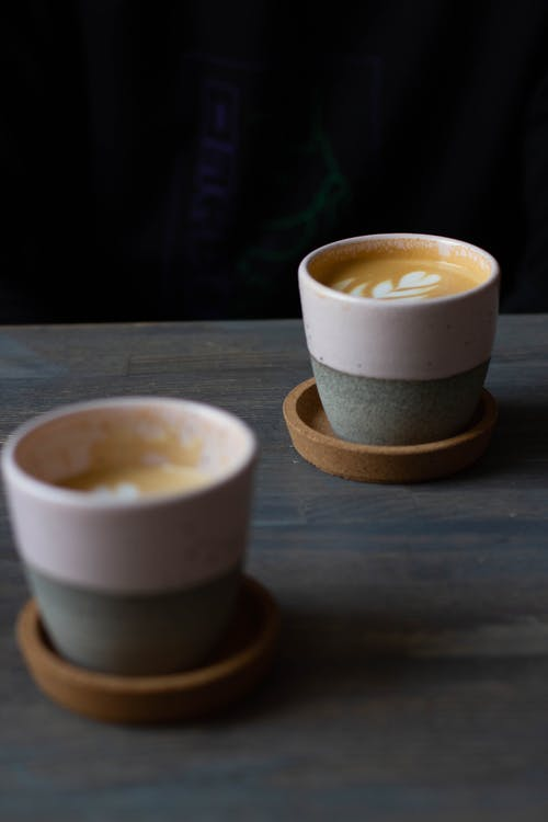 Cups with fresh aromatic cappuccino on table