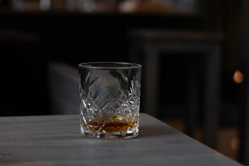 Cut glass with aromatic cognac on bottom placed on wooden table in dark living room