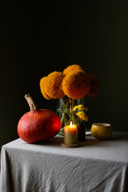 Table with pumpkin and blooming flowers