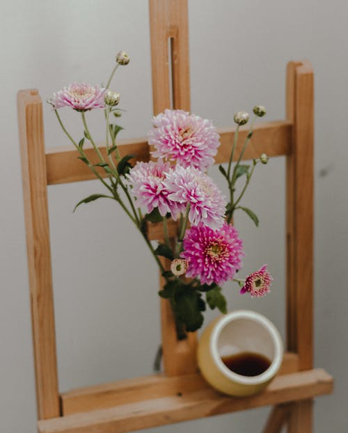 Flowers and coffee in mug on wooden easel