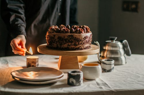 Person lighting candle placed near chocolate cake