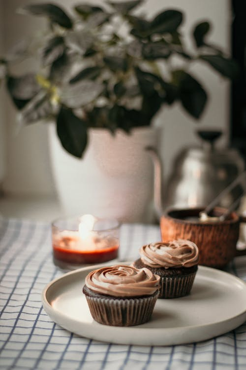 Delicious chocolate cupcakes with cream on plate
