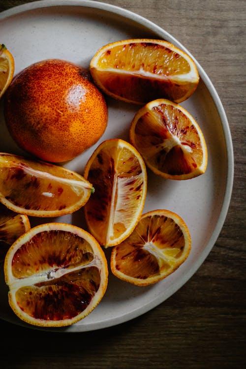 Cut ripe juicy oranges on ceramic plate