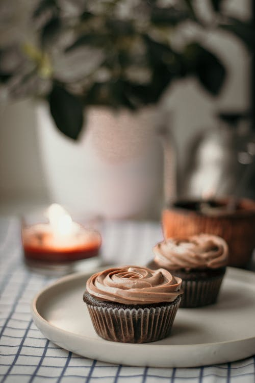 Delicious cupcakes with cream topping at kitchen