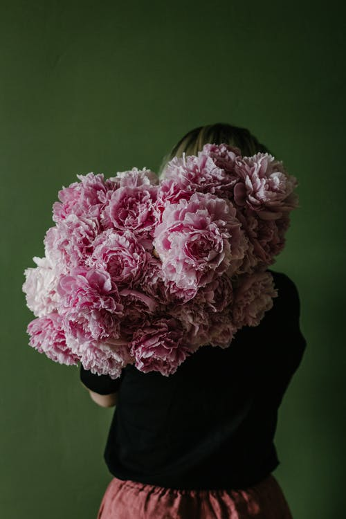 Back view of anonymous female with bunch of fresh flowers standing against green wall