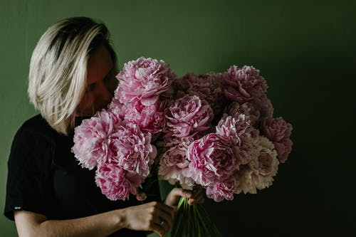 Female with dyed hair smelling bouquet of fragrant pink blooming peonies against green background