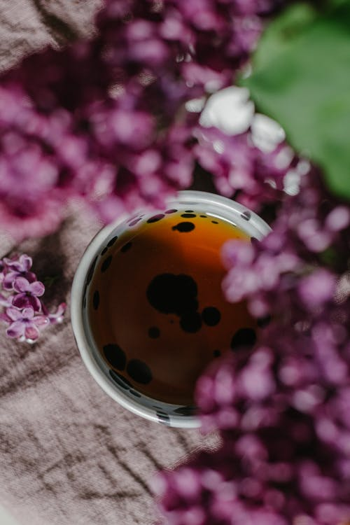 Top view of cup of tea placed near fresh branches of lilac with purple petals