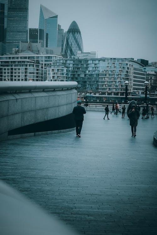 People Walking on White Concrete Bridge