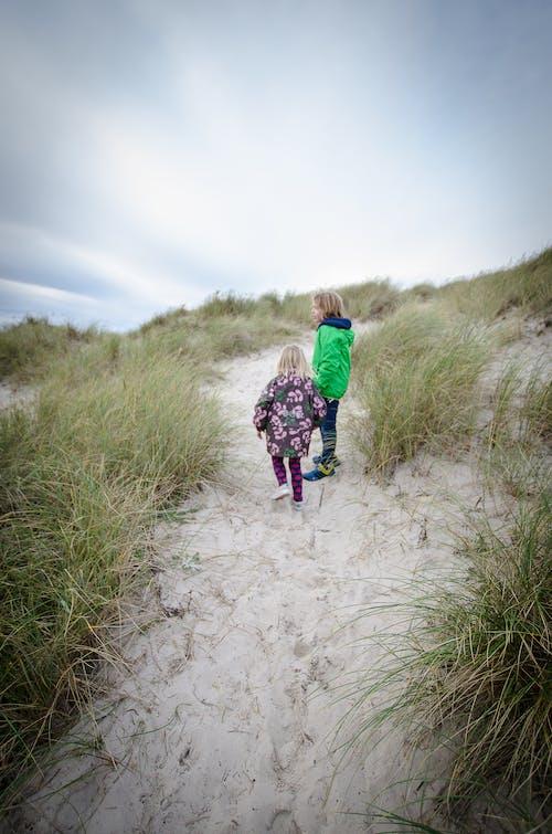 çocuklar, kardeşler, kum tepeciği, plaj içeren Ücretsiz stok fotoğraf
