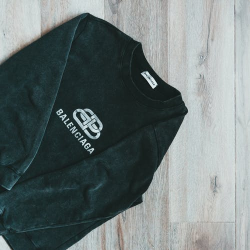 From above of stylish comfy long sleeved pullover with brand logo placed on wooden floor
