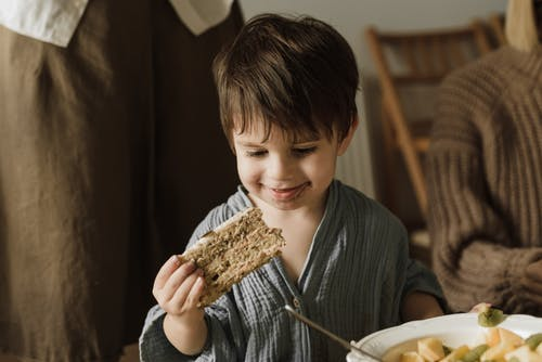 Boy in Gray Long Sleeve Shirt Holding a Bread