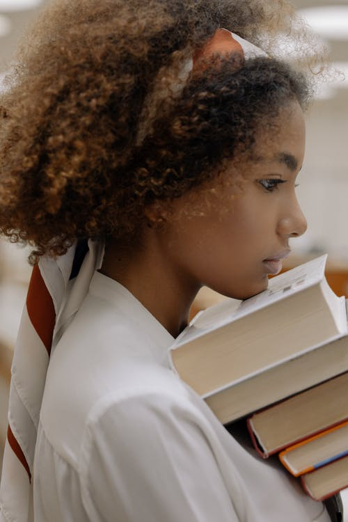 Photo Of Woman Leaning Her Head On Top Of Books