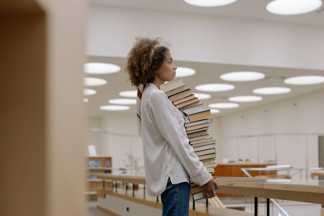 Photo Of Woman Carrying Pile Of Books