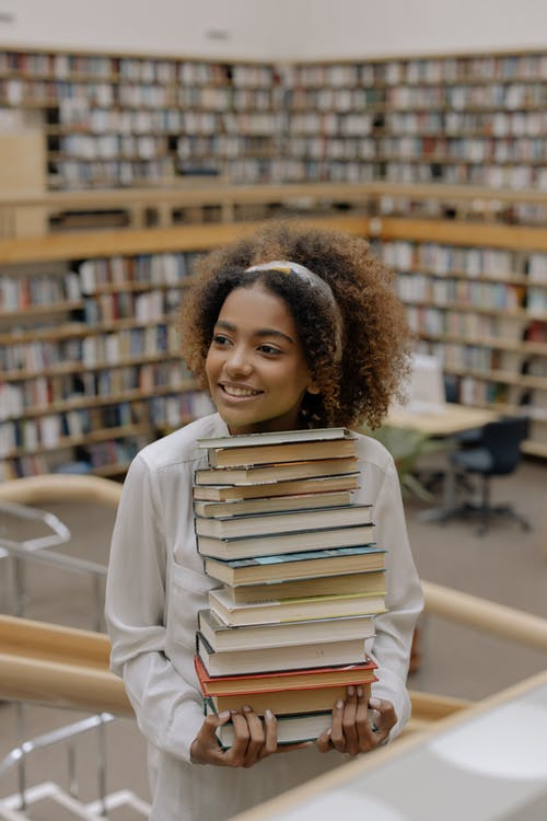 Photo Of Woman Carrying Stack Of Books