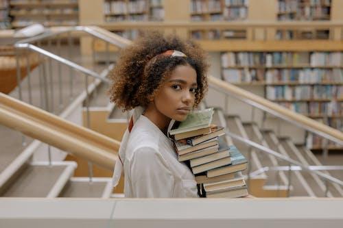 Photo De Femme Portant Une Pile De Livres