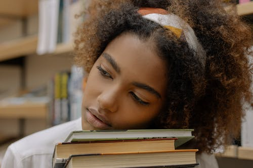 Photo Of Woman Resting Her Head On Top Of Books
