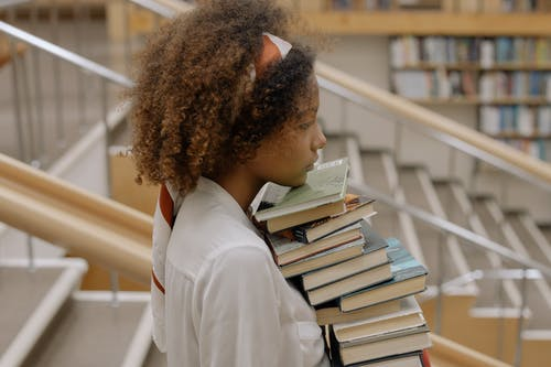 Side View Photo Of Woman Carrying Books