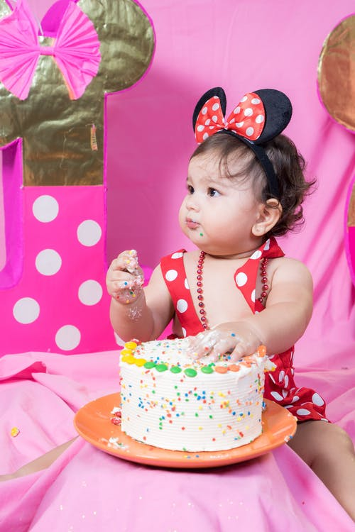 Girl in Pink and White Polka Dot Tank Top Holding White and Pink Cake