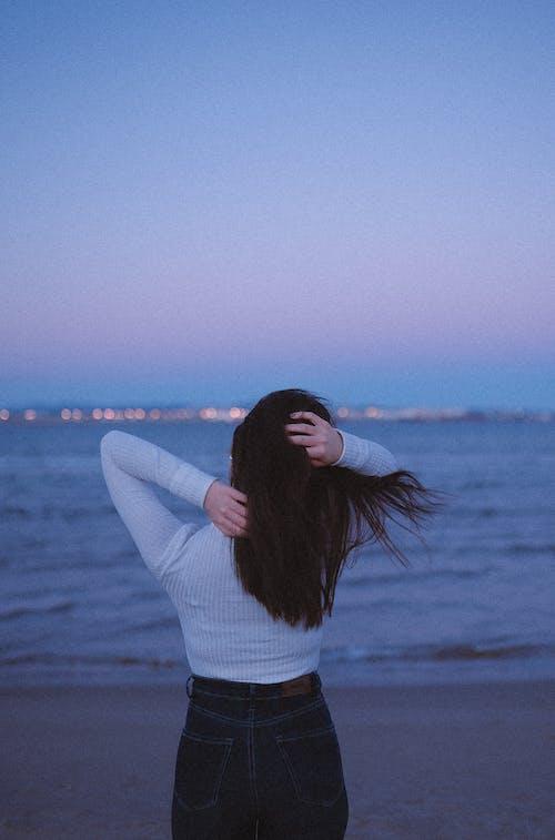 Unrecognizable woman on sandy seashore in evening