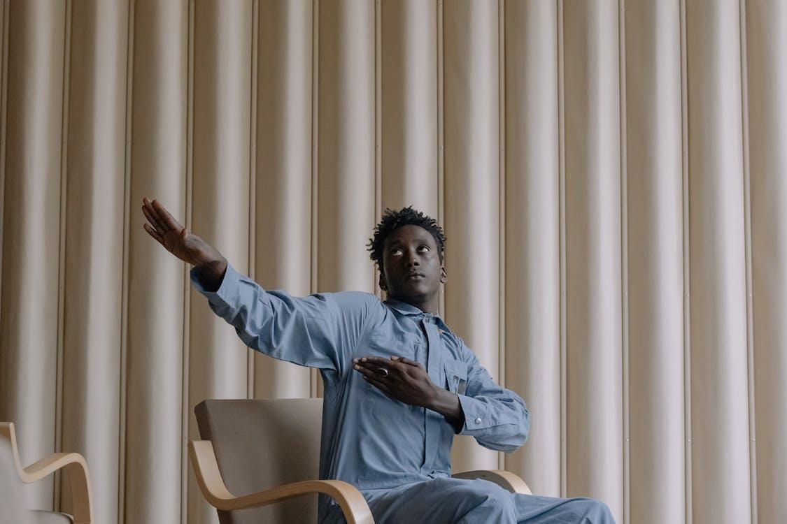 Man in Blue Dress Shirt Sitting on White Armchair