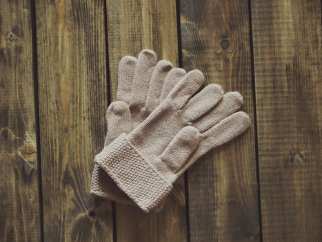 White Gloves on Brown Wooden Surface
