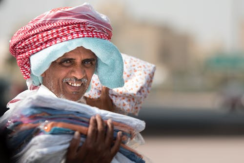 Man Holding Clothing While Smiling