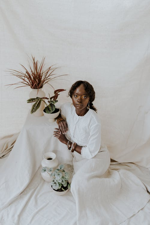 From above of content African American female in long white dress looking at camera on white fabric near potted plants